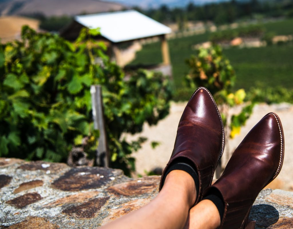 Image of a woman's feet up on a wall overlooking a vineyard.