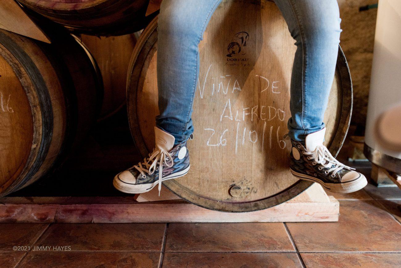 Winemaker sitting on barrels